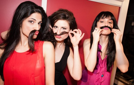 Three woman using their hair as a mustache