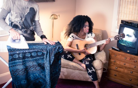 Woman playing guitar with man ironing